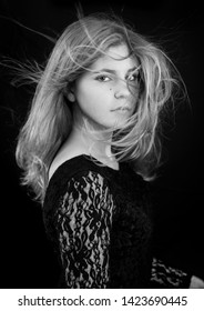 May 2016. Beautiful 18 year old blond girl on a black background, Flers, France. Studio lighting. Black and white model portrait. She is wearing a black lacy dress, her hair blowing in the wind.