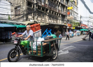 May 2017, Bangkok, Thailand, a streetseller on a motorbike with sidecar waits at a crossing his sidecar loaded with fresh eggs and plastic baskets and stools