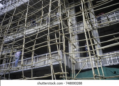 May 2017, Dharamsala, India, McLeod Ganj,construction workers stand on the bamboo scaffolding built on the outside of a new hotel building