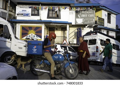 May 2017, Dharamsala, India, McLeod Ganj, a very busy square in the small hill town with people and 4 wheel and two wheel vehicles and men and animal