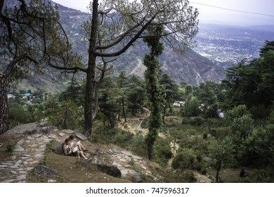 May 2017, Dharamsala, McLeod Ganj, Himalayas,a  young tourists couple with books sits on some stone steps with a panoramic  view of the plains