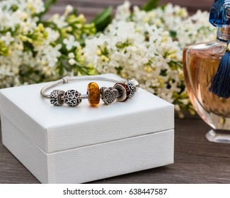 May, 2017. Minsk, Belarus. The bottle of perfume of the famous brand and the fashion jewelery of Pandora. Gift box. Charm bracelet. Amber. For woman. A gift to the holiday. Wedding. Birthday. Love.