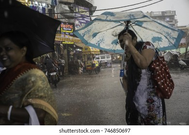 May 2017, New Delhi, India, two men on a scooter driving through heavy rain while one is holding the umbrella to protect both from the rain