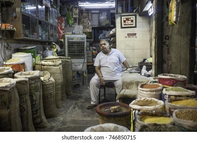 May 2017, New Delhi, India, a heavy set man sits in his shop full of sacks of rice and pulses in different colors