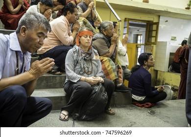 May 2017,Dharamsala, India, Mcleod Ganj, main temple Theckchen Choeling , a European woman sits amongst Tibetans during teachings the Dalai Lama is giving