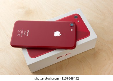 May 2018. Apple iPhone 8 (PRODUCT) RED and box lies on a wooden table. A new smartphone from the company APPLE close-up on a wooden surface.