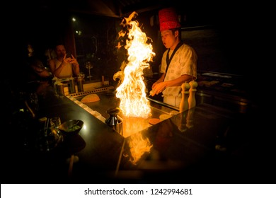 May, 2018 - Ari atoll, Maldives: Japanese Chef cooking lobster on a Teppanyaki grill with big flame. Gourmet food and food show in luxury restaurant.