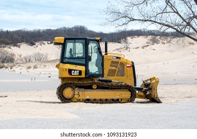 May 2018 Michigan USA; a large bulldozer is ready to move sand at Warren dunes state park, to clean up blowing sand  from the parking lot, and reform the beach before the summer crowd arrives