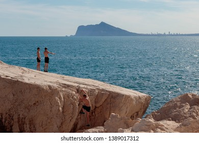 MAY 2019 - CALPE, SPAIN: Young people play on the Calpe's rocks with Benidorm skyline on the background