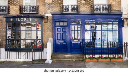 """MAY 2019. Charming english street in center London, England, United Kingdom. Beautiful blue shop facade with """"Floris"""" written on it. Brick walls. Daytime. Colorful building."""