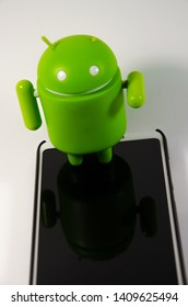 May 2019. Los Angeles,USA. Green plastic Android figure on a white background and with a smartphone. Figure, logo Android, Google