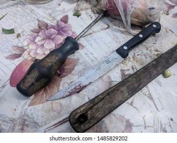 May 2019, Mehedinti, Romania. Screwdriver, knife and a wooden spoon on a table, country side. Stainless steel inox kitchen knife, dirty old tools on a plastic flowery mat