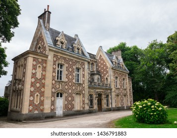 May 2019. Music academy of Flers (Normandy, France). French conservatory. Beautiful ancient building, mansion with a stone & red brick architecture, surrounded by nature. Cloudy day. Wide-angle shot.
