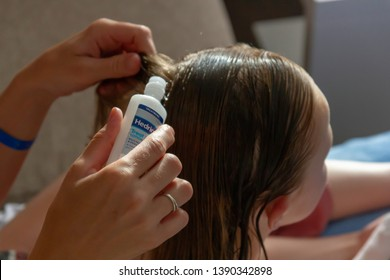May 2019, Stafford UK. Mother treating daughter's hair against lice. Checking For Lice. Hedrin Treat & Go, kills hed lices and eggs, no fuss. A leave-in treatment, wash your hair later.