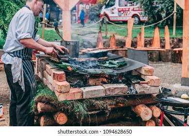 May 20th, 2018, Cobh, Ireland - a man cooking salmon covered with leaves and meat over a rustic barbecue