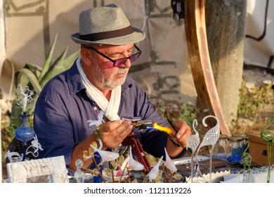 May 22, 2018, Marmaris, Turkey: An elderly glassblower man works in the street.