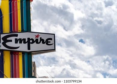 May 25 2018 - Livingston, Montana: Retro neon sign for the Empire Movie Theater against a cloudy sky, in downtown Livingston Montana
