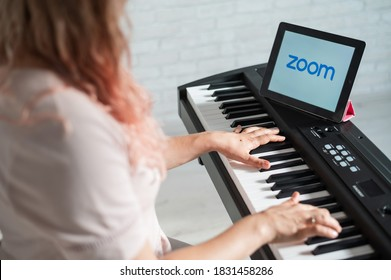 May 25, 2020 Novosibirsk Russia: Caucasian woman remotely learns to play the piano using the ZOOM app on a digital tablet