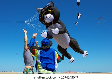 May 26, 2013 - Wildwood, NJ, USA: A giant cat-shaped show kite looks as though it is pouncing on the men charged with sending it skywards at the Wildwoods International Kite Festival.