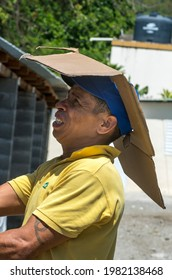 May 26, 2021 San Jose De Ocoa, Dominican Republic. Dramatic image of a ingenious Dominican man wearing a cardboard hat cutout to fit his cap in the hot tropical Caribbean heat.