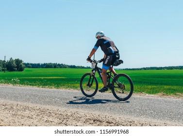 May 26-27, 2018 Naliboki,Belarus All-Belarusian amateur marathon Naliboki A man is riding a bike along the trail in the field