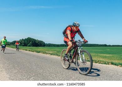 May 26-27, 2018 Naliboki,Belarus All-Belarusian amateur marathon Naliboki A man runs alongside a group of cyclists on the road