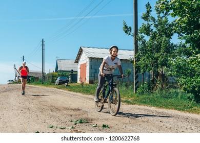 May 26-27, 2018 Naliboki,Belarus All-Belarusian amateur marathon Naliboki A girl rides a bicycle on the road between the houses