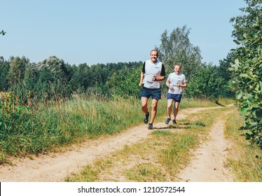 May 26-27, 2018 Naliboki,Belarus All-Belarusian amateur marathon Naliboki Two men run along the path in the field next to the forest