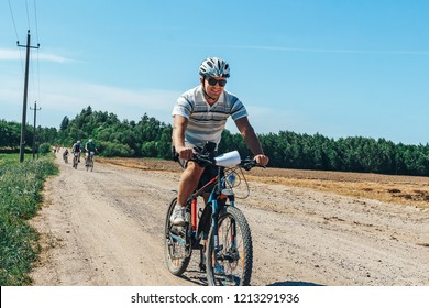 May 26-27, 2018 Naliboki,Belarus All-Belarusian amateur marathon Naliboki A man riding a bicycle on the road next to the field