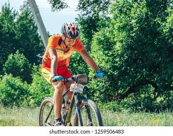 May 26-27, 2018 Naliboki,Belarus All-Belarusian amateur marathon Naliboki A man with a child riding a bike on the road