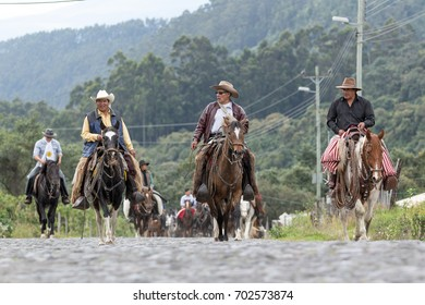 May 27, 2017 Sangolqui, Ecuador: cowboys from the Andes region on horseback traveling to a rural rodeo on a cobblestone country road
