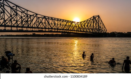 May 27,2018. Kolkata, India. Silhouette of Howrah Bridge at the time of Sunrise.  People bathing and making rituals in the River Ganges.