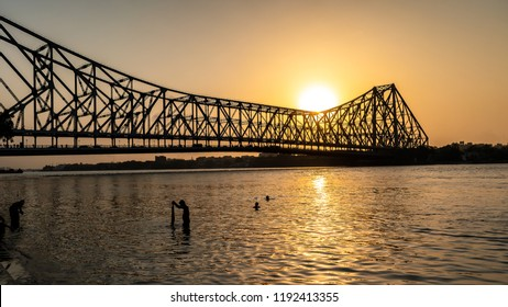 May 27,2018. Kolkata, India.Silhouette of Howrah Bridge at the time of Sunrise.  People bathing and making rituals in the River Ganges.