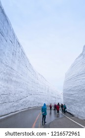 MAY 28, 2013 Toyama, Japan - Exotic nature view of road between snow wall at Tateyama Kurobe Alpine Route with tourists enjoy cold wintrer scene