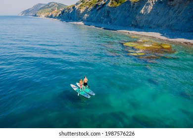May 28, 2021. Anapa, Russia. Couple traveling on stand up paddle board at sea. People walking on Red paddle sup board in transparent sea. Aerial view