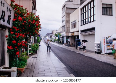 MAY 29, 2013 Matsumoto, JAPAN - Old Japanese Edo architecture building with ceramic tiles roof  in Nakamachi dori street area with local people under umbrella on rainy day