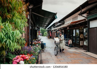 MAY 29, 2013 Matsumoto, JAPAN - Old Japanese Edo architecture building with ceramic tiles roof became plant flower shop in Nawate street area. Old Japanese guy with bicycle on rainy day