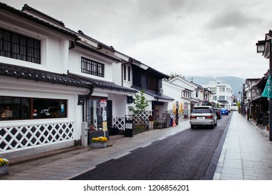 MAY 29, 2013 Matsumoto, JAPAN - Old Japanese Edo architecture building with ceramic tiles roof  in Nakamachi dori street area with cars on rainy day