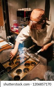 MAY 29, 2013 Matsumoto, JAPAN - Woman pastry chef cooking deep fried Red bean paste Manju - Japanese style Baozi buns special sweet of Nagano - Matsumoto