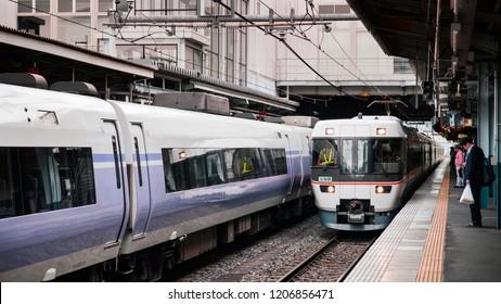 MAY 29, 2013 Nagano, Japan - Azusa express and Shinano line trains arriving at platform of  JR Chuo Main line at Matsumoto station with Japanese passengers waiting behind yellow line