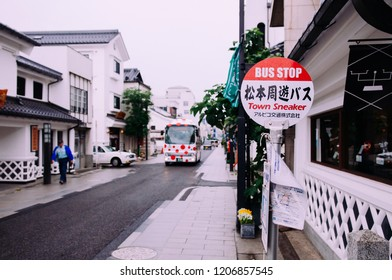 MAY 29, 2013 Nagano, Japan - Matsumoto city sightseeing bus stop sign on small street with old vintage white building in tourist area near art museum
