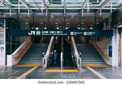 MAY 29, 2013 Nagano, Japan - Castle gate entrance with stairs, escalators and information sign of Matsumoto station with passengers back to camera. Cold colour tone image