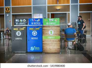 May 29, 2019. Austin–Bergstrom International Airport, Austin, Texas. Recycling bins: landfill, recycle, compost