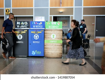 May 29, 2019. Austin–Bergstrom International Airport, Austin, Texas. Recycling bins: landfill, recycle, compost, Passenger is  taking a glass bottle to recycling bin. Focus on recycling bins.