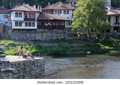 MAY 3, 2015: Unidentified girl sits by the Yantra river in Asenov district of the city