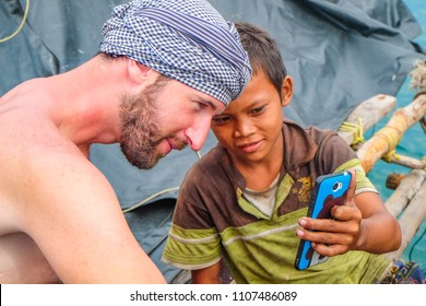 May 3 2018 - Myeik Archipelago, Myanmar. Burmese boy on fishing boat, showing tourist a game on a mobile phone