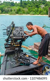 May 3 2018 - Myeik ARchipelago, Myanmar. Fisherman fixing a boat engine