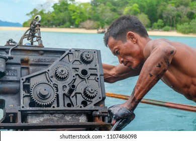 May 3 2018 - Myeik Archipelago, Myanmar. Fisherman fixing boat engine.