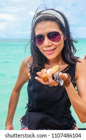 May 3 2018 - Myeik Archipelago, Myanmar. Thai woman holding collection of pretty shells from the beach