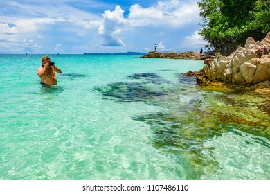 May 3 2018 - Myeik Archipelago, Myanmar. Photographer standing in the shallows and taking photo of beautiful tropical island beach.